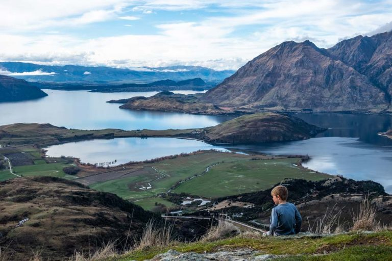 Nathan from Backyard Travel Family sits an looks over the view over Lake Wanaka from the Rocky Mountain wanaka track