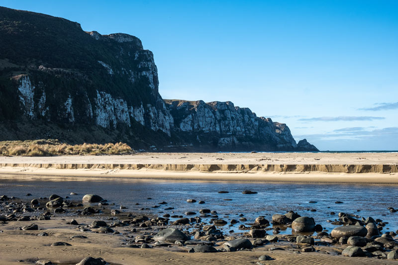 Purakaunui Bay is perhaps one of the most beautiful things to see in the Catlins NZ, with towering cliffs over the golden sand beaches