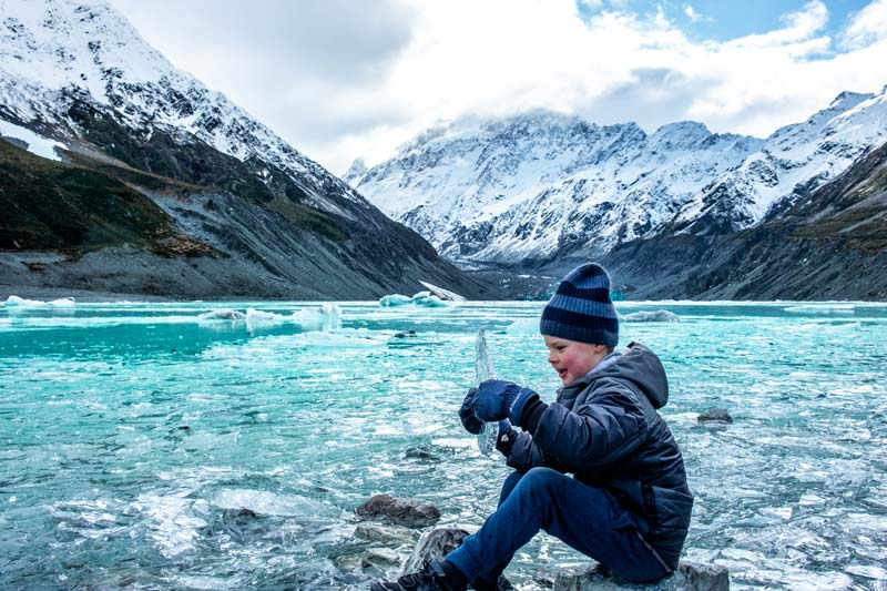 Nathan from Backyard Travel Family picks up a huge piece of ice at the Hooker Valley Track in winter