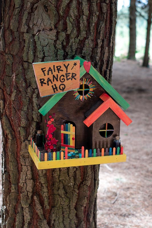 """Colourful wooden fairy house, with the sign """"Fairy Ranger HQ"""" as found on the Bottle Lake Fairy Forest, Christchurch"""