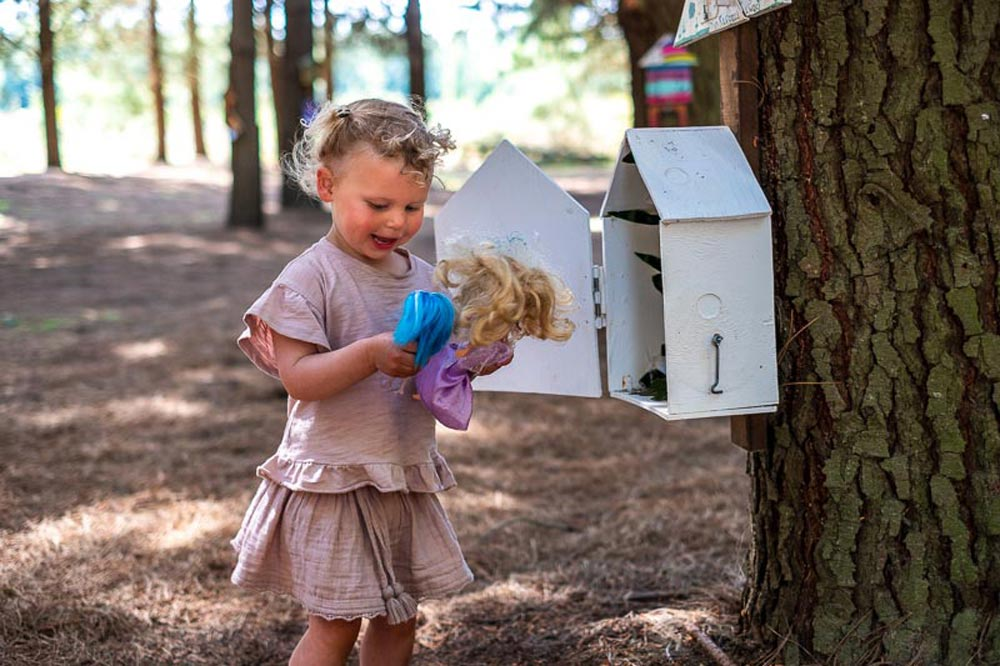 Emilia from Backyard Travel Family finds a toy doll inside a fairy house in the Bottle Lake Forest Fairy Walk in Christchurch