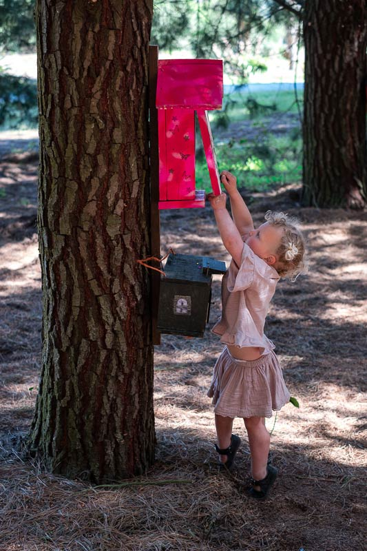 Emilia from Backyard Travel Family opens up a bright red fairy door in the Bottle Lake Forest Fairy Village, Christchurch
