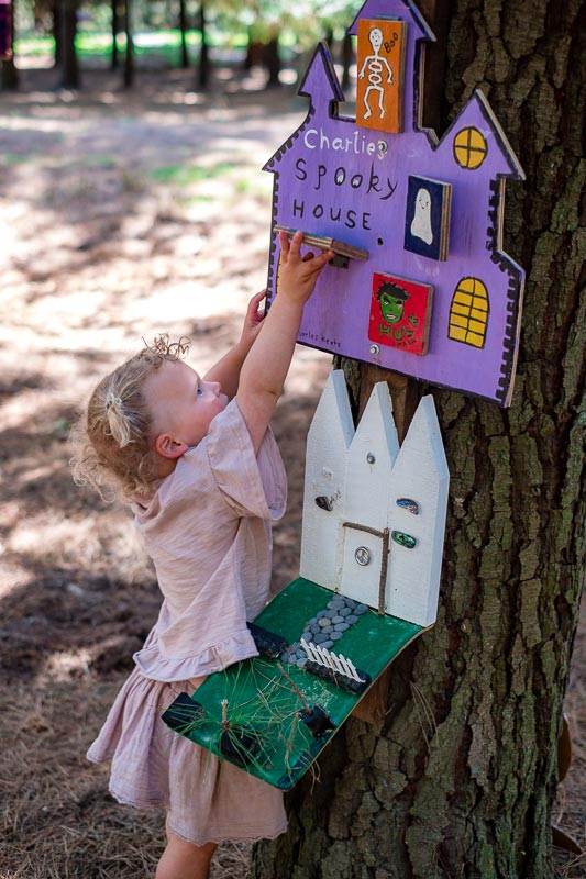 Emilia from Backyard Travel Family is exploring a Christchurch fairy door walk at Bottle Lake Forest