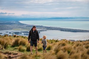 Father and son look at visit the Christchurch Gondola, with epic views overlooking the Canterbury Coastline, New Zealand