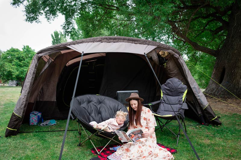 Jen and Emilia from Backyard Travel Family sit in the awning of their tent, reading a magazine under the trees