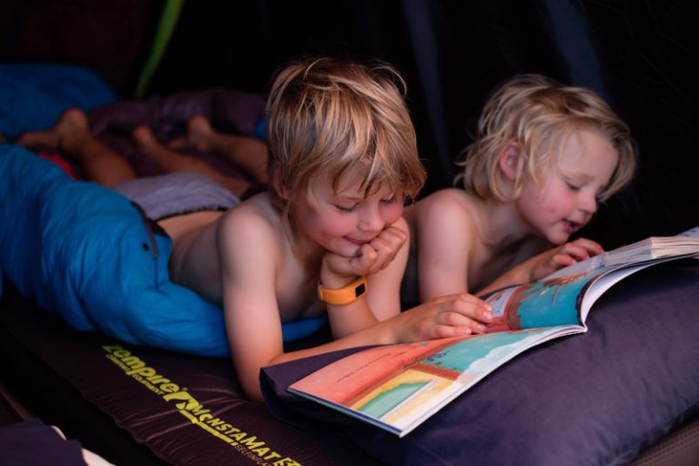 Nathan and Kipton from Backyard Travel Family lie on their Monstamat camping mat before bed
