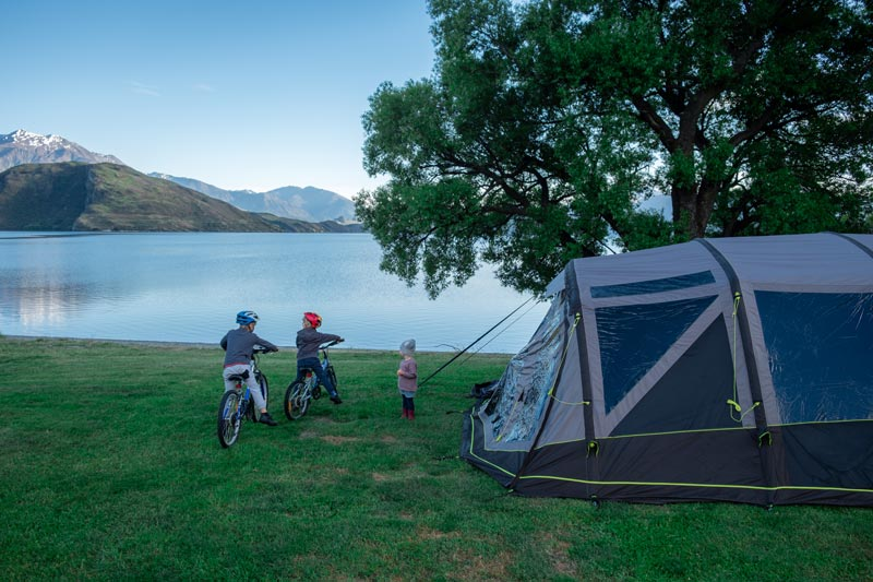 Family look over Lake Wanaka from their campsite at Glendhu Bay