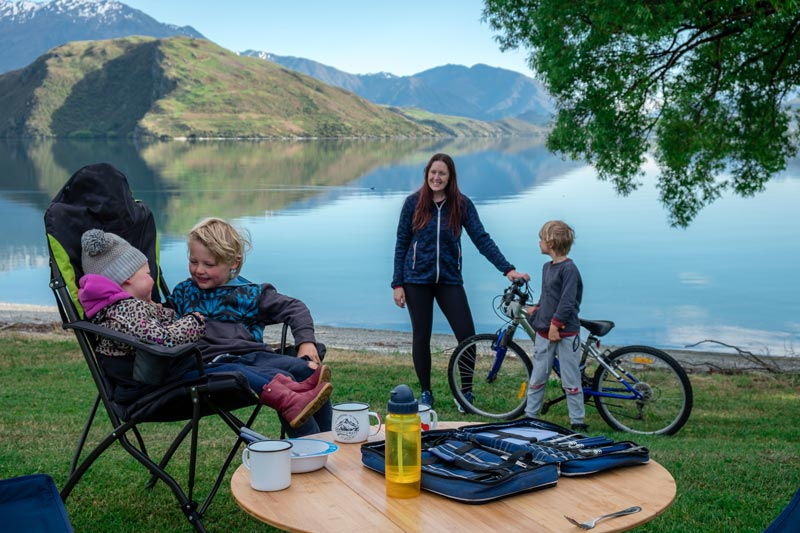 Family sit on their camping chairs overlooking Lake Wanaka