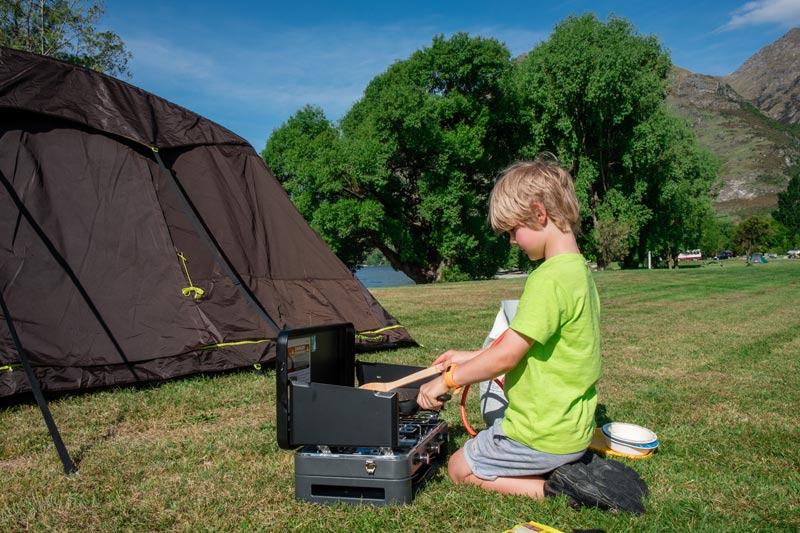 Nathan from Backyard Travel Family cooks a camping dinner on his Zempire Deluxe Cooker with grill
