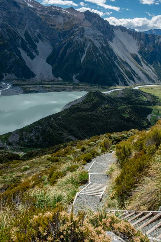 Looking down at the 2200 stairs on the Sealy Tarns Track, an uphill Mt Cook walk, with Mueller Lake in behind