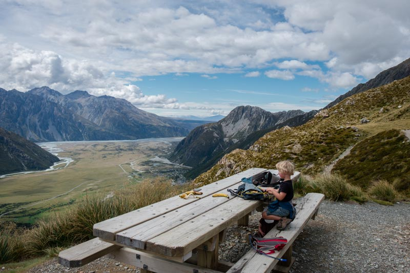 Kipton sitting at the large wooden picnic table at the top of the Sealy Tarns Track, Mt Cook National Park, New Zealand