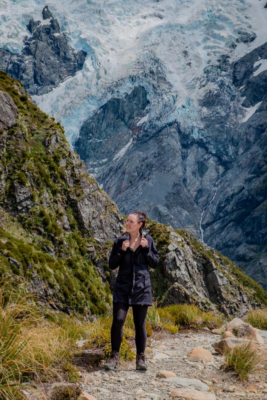 Jen looking at mountain views, standing in front of a glacier at the top of the Sealy Tarns Mt Cook Track
