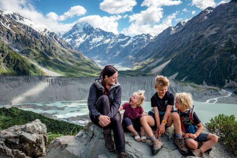 Backyard Travel Family sit at a viewpoint on the Sealy Tarns Track overlooking Mt Cook