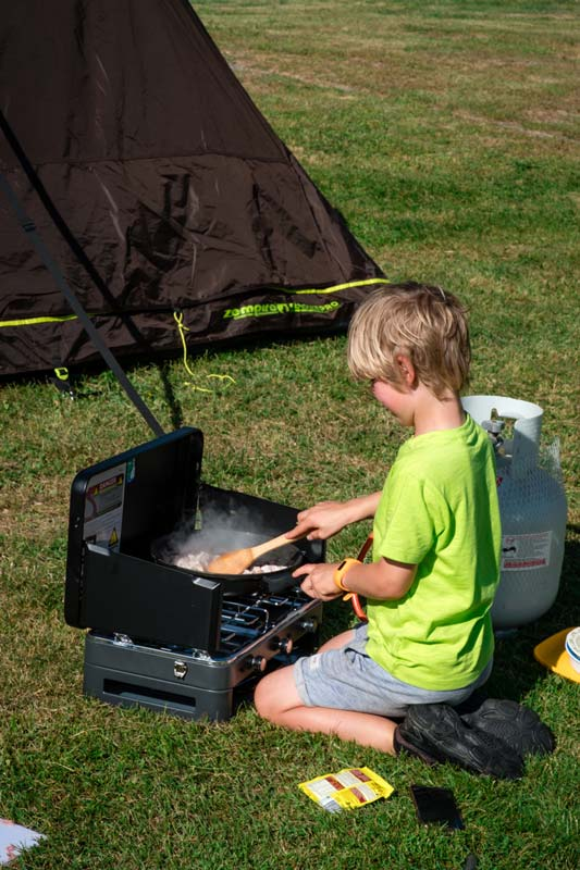 Nathan from Backyard Travel Family cooks dinner at a New Zealand campground