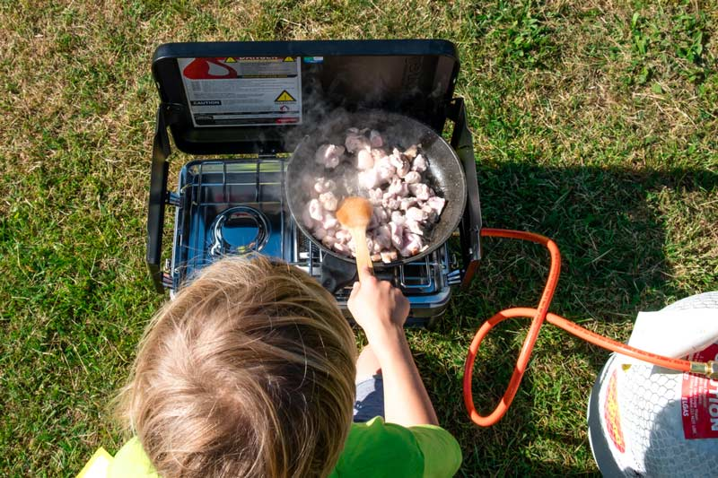 Nathan from Backyard Travel Family cooks chicken for dinner on the Zempire Deluxe Burner and Grill