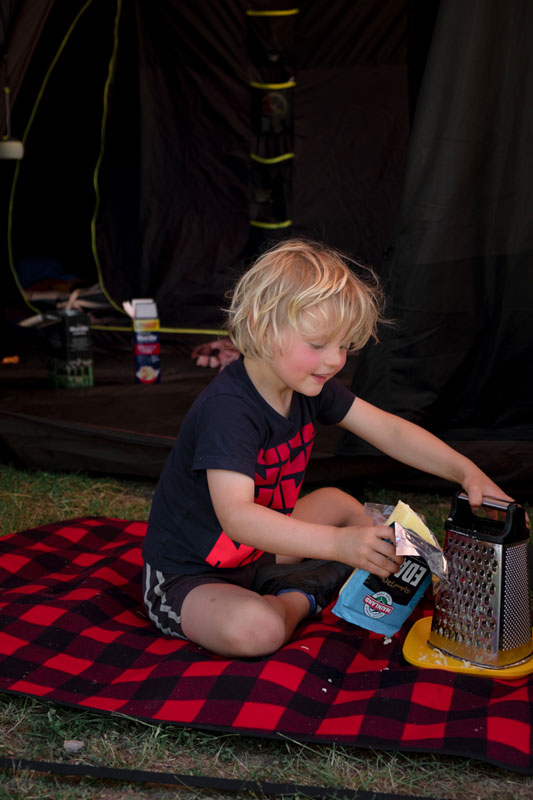Kipton from Backyard Travel Family grates cheese for dinner while sitting on a plaid picnic mat