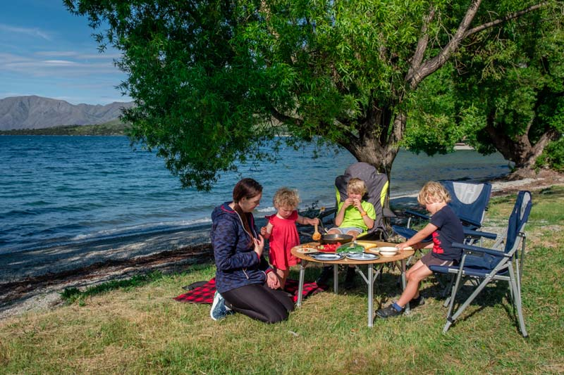 Backyard Travel Family make dinner beside Lake Wanaka while sitting at table and chairs