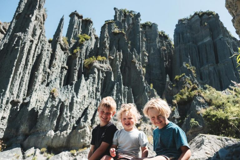 3 happy kids sitting in front of the Putangirua Pinnacles, unique rock formation in the Wairarapa