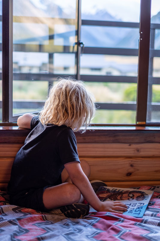 Child looking out the window of a private room at the mountains, at YHA Aoraki Mt Cook