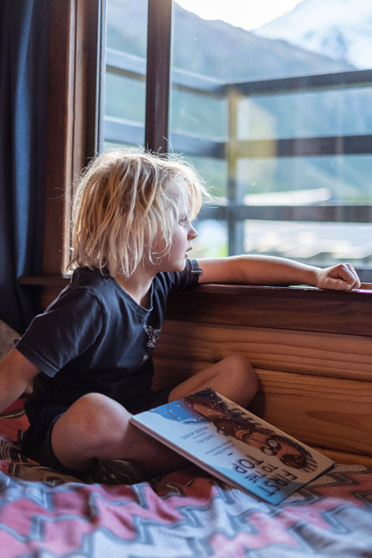 Young boy reading a book, looking out the window at the mountains at YHA Aoraki Mt Cook