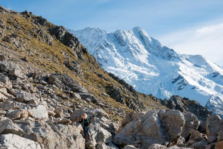 Kipton from Backyard Travel Family climbs boulders on route to Mueller Hut, with the snowy Southern Alps in the background.