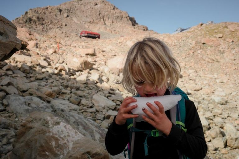 Kipton eating ice with the red Mueller Hut in the backyground