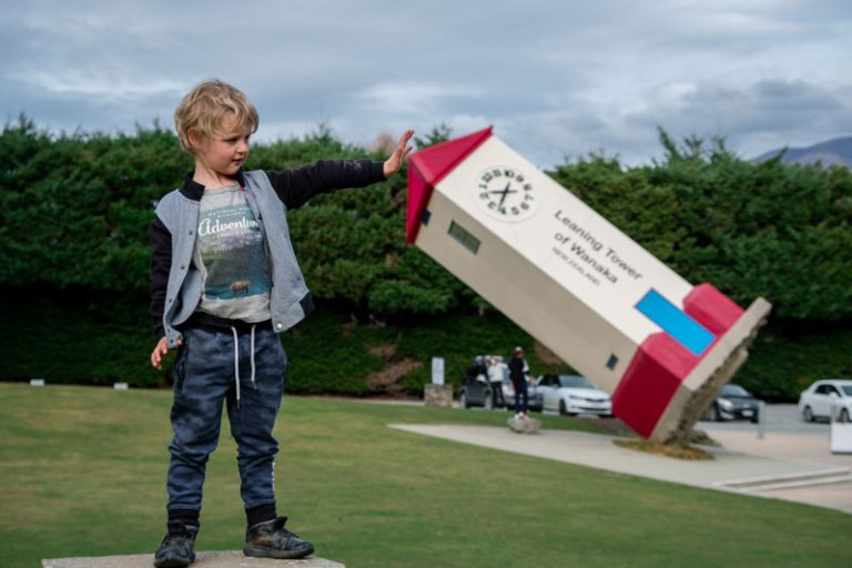 Kipton from Backyard Travel Family uses an illusion to hold up the Leaning Tower of Wanaka, NZ