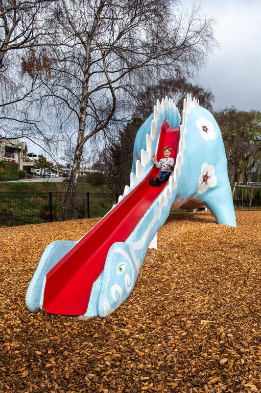 Nathan slides down the blue and red dinosaur park