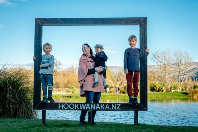Backyard Travel Family stand inside a wooden frame, in front of a manmade lake with salmon at Hook Wanaka NZ