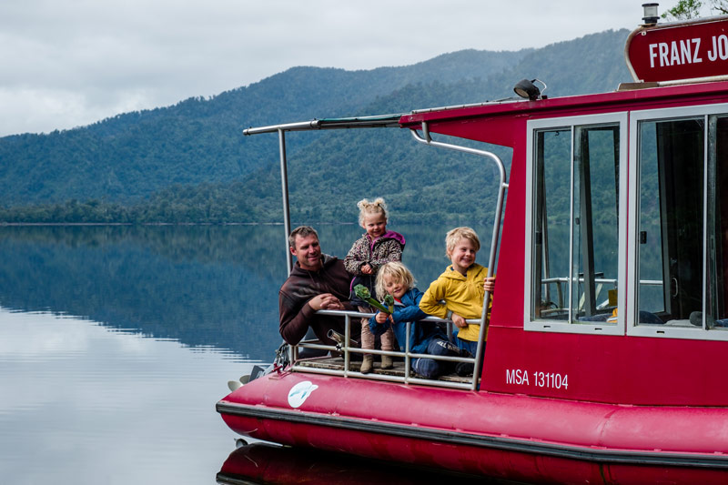 Backyard Travel Family sit on the back of the Franz Josef Wilderness Tours boat cruise on Lake Mapourika at Franz Josef Glacier