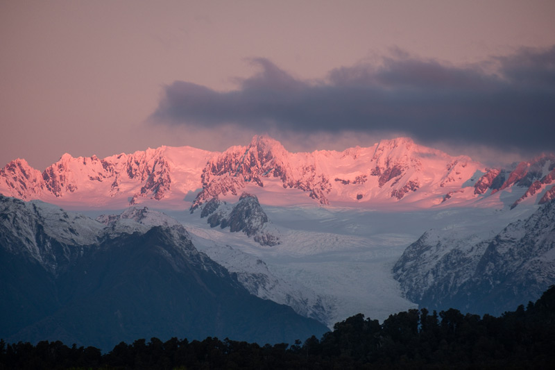 Pink hues of sunset on Mt Tasman and Mt Cook from Gillespies Beach on the West Coast
