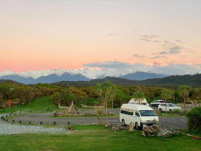 Sunset over Mt Cook and Mt Tasman, with orange hues lighting up the mountains taken from Gillespies Beach Fox Glacier West Coast NZ