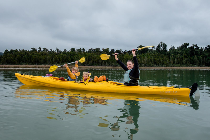 Mum and two children paddle a three person kayak in the Okarito Lagoon on the West Coast of New Zealand