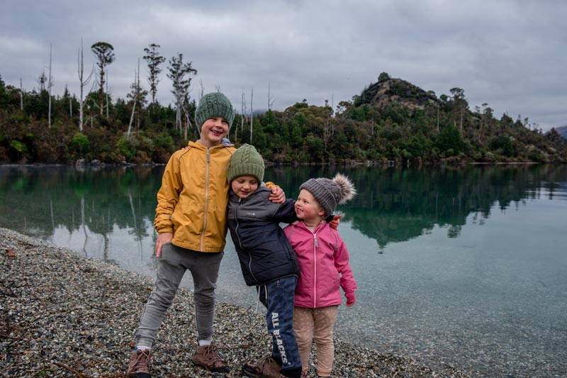 Three kids from Backyard Travel Family embrace on the beach at Bobs Cove Queenstown