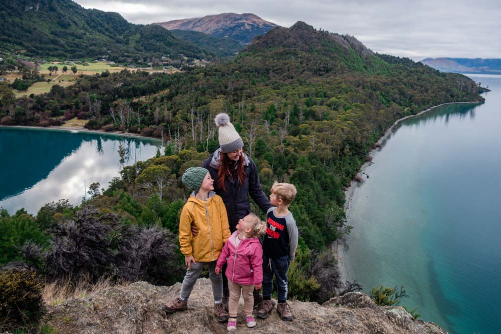 Backyard Travel Family delight in reaching the top of Picnic Point, Bobs Cove. With incredibles blue green waters of Lake Wakatipu in behind them.