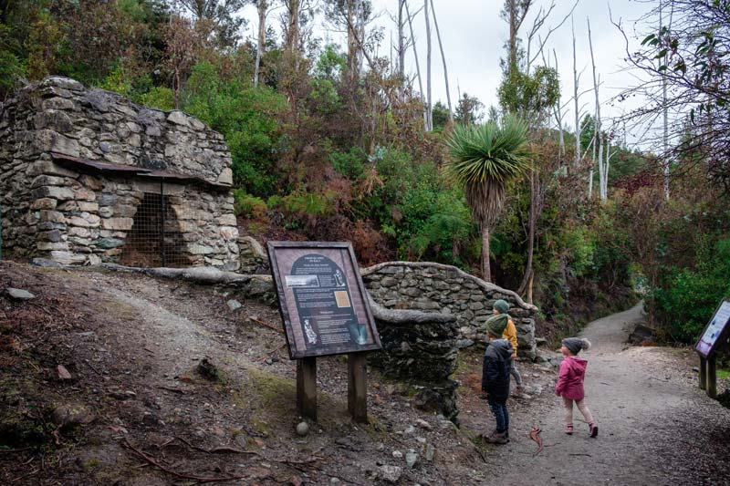 Backyard Travel Family children learn about the history of the limestone kilns on the Bobs Cove walk Queenstown
