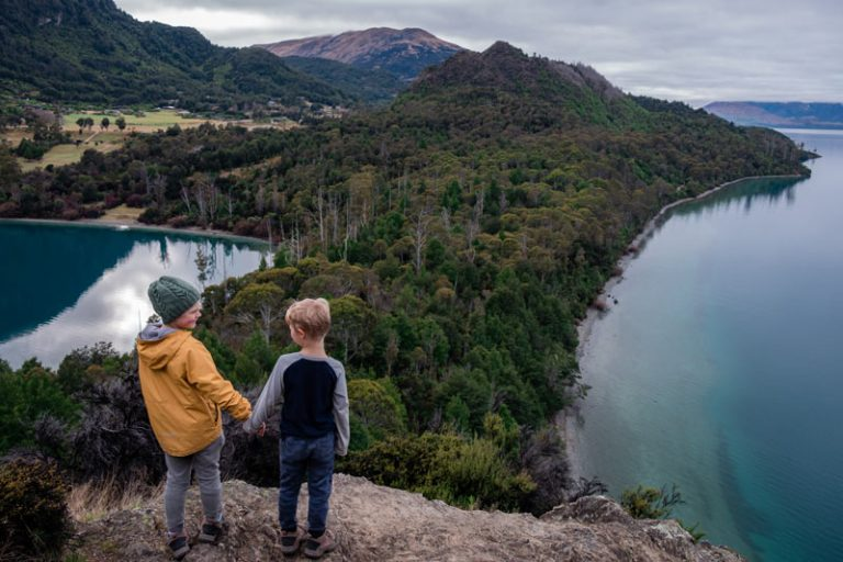 Backyard Travel Family boys hold hands while they look lovingly at each other as they look over Lake Wakatipu and Bobs Cove in Queenstown, New Zealand