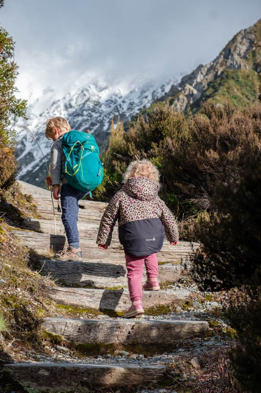 2 children walk up the stairs on the Red Tarns Track, with a snowy mountain backdrop
