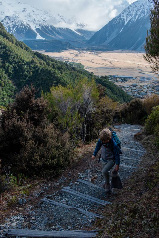 Nathan from Backyard Travel Family walks up the stairs on the Red Tarns Track, a steep uphill walk in Mt Cook, with views of Aoraki Mt Cook and Mt Cook Village