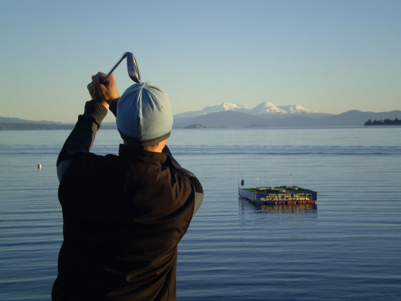 One of the most fun things to do in Taupo is to try the hole in one challenge. A golfer admires his swing on a still morning as he hits the ball on the platform into the middle of Lake Taupo