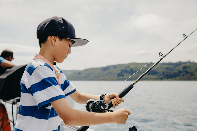 A boy looks down at his fishing road, while boating on Lake Taupo, New Zealand