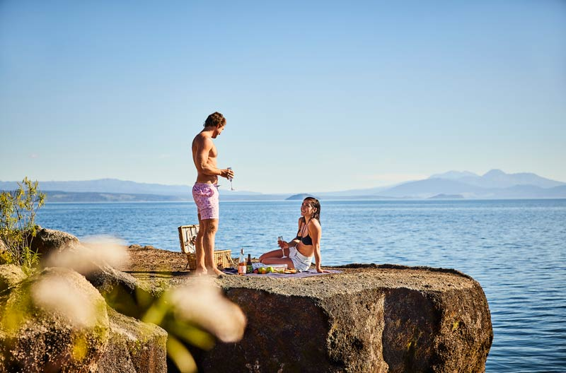 A couple drink wine and have a picnic by Lake Taupo New Zealand