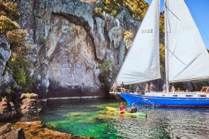 A sail boat visit the Maori Rock in Taupo, one of the best things to do in Taupo with kids